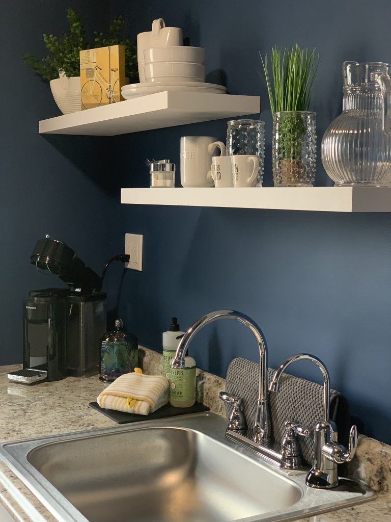 Kitchenette shelves with dishes for use during stay, Nespresso machine, and filtered water spout.